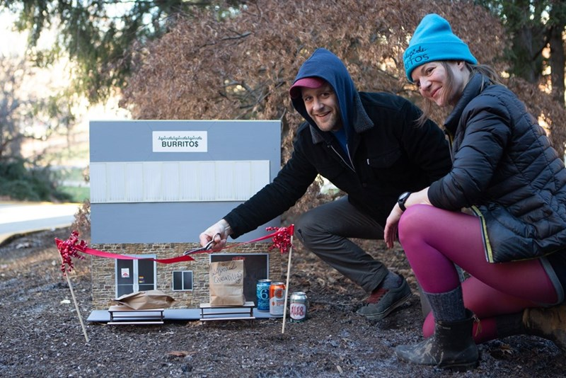 tiny burrito restaurant for squirrels | two people smiling and crouching by a miniature burrito restaurant called squirrelssquirrelssquirrels and cutting the ribbon tied at the front of it
