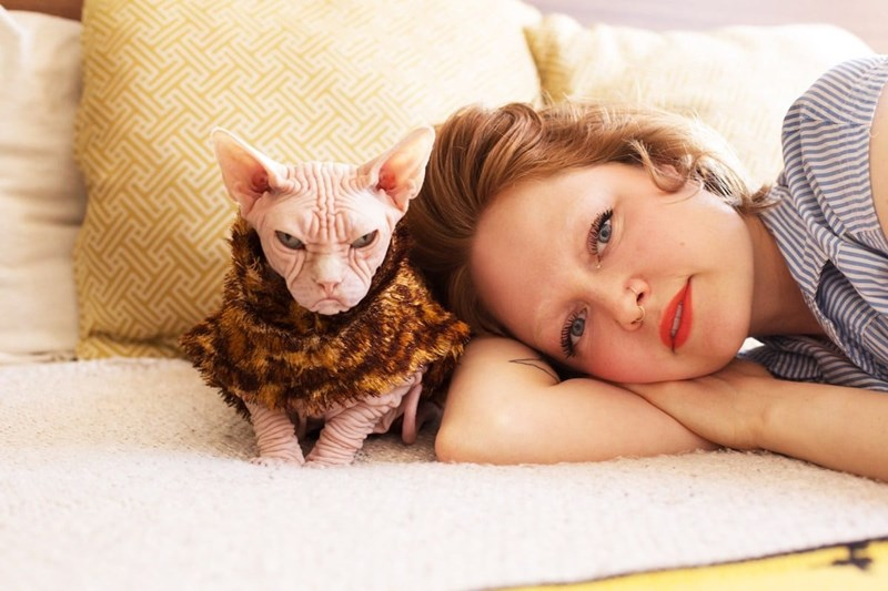 photography project- girls and their cats | woman with red hair and very light eyebrows lying on her side next to a grumpy looking bald sphynx cat wearing a leopard print sweater