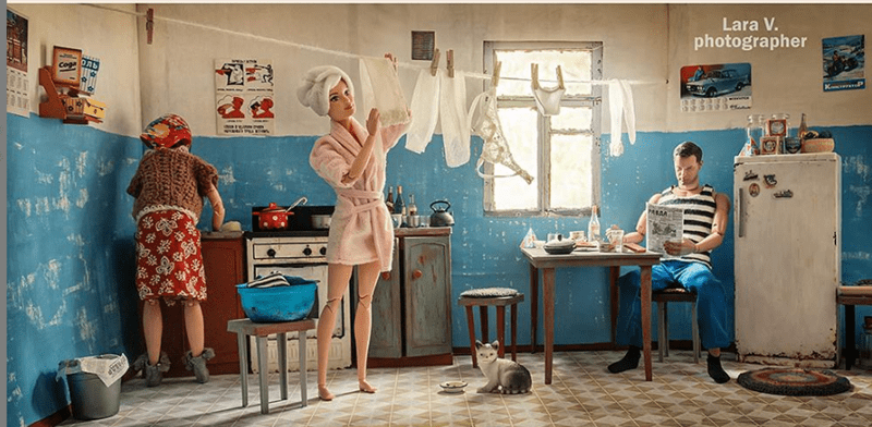 Barbie and ken living in the USSR | dollhouse designed to look like an old apartment in the soviet era. barbie hanging laundry to dry on a rope in the kitchen, her babushka is wearing a scarf over her head and is cooking something in the background. ken is sitting by the table wearing a tank top and reading the newspaper.