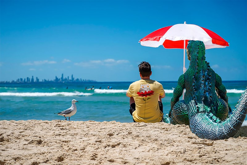 photoshopping giant godzilla to photos | sandy beach seagull man in yellow t-shirt and godzilla sitting on the beach sunny day under a red and white parasol