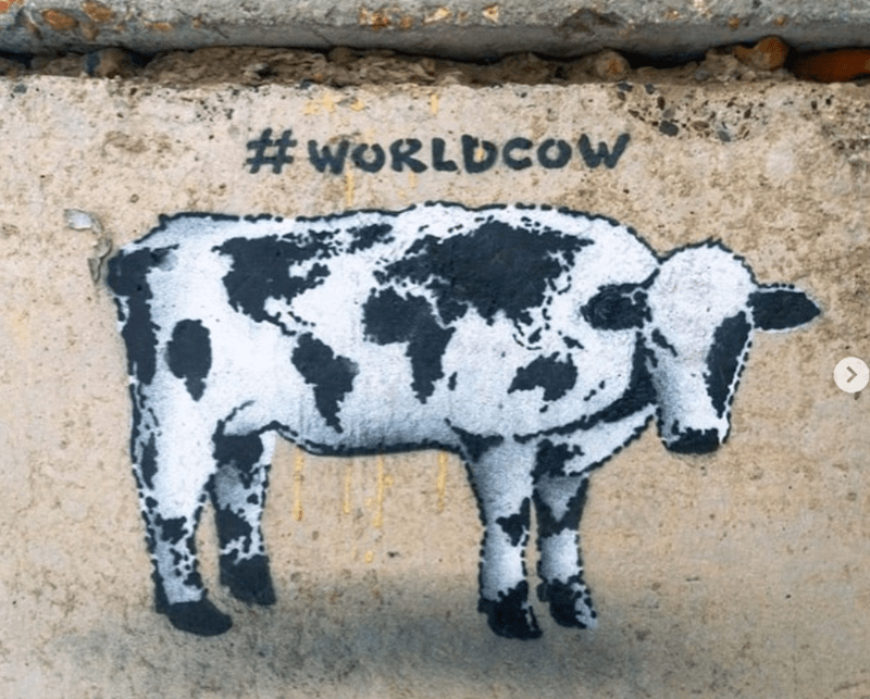 street artists paint cows around the world as a message of unity | hashtag WORLDCOW black and white graffiti of a cow on a road near a pavement