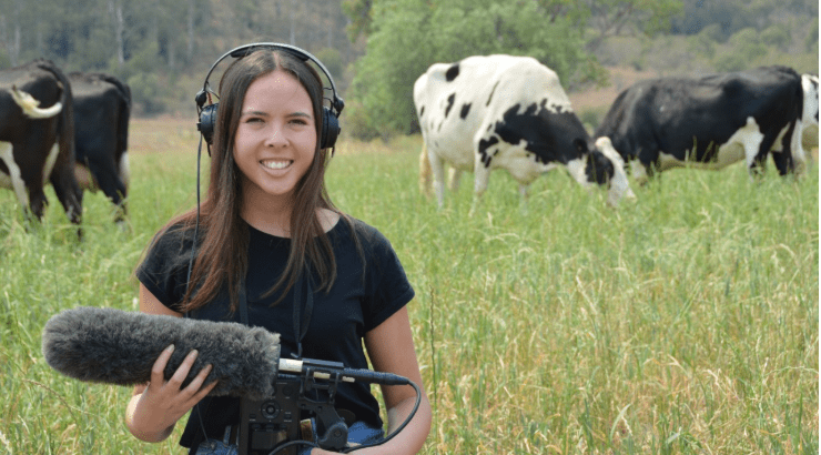 New Study Finds Cows Express Their Feelings With Different Sound of Moos | woman with headphone holding a large microphone while standing in a grassy field in front of cows