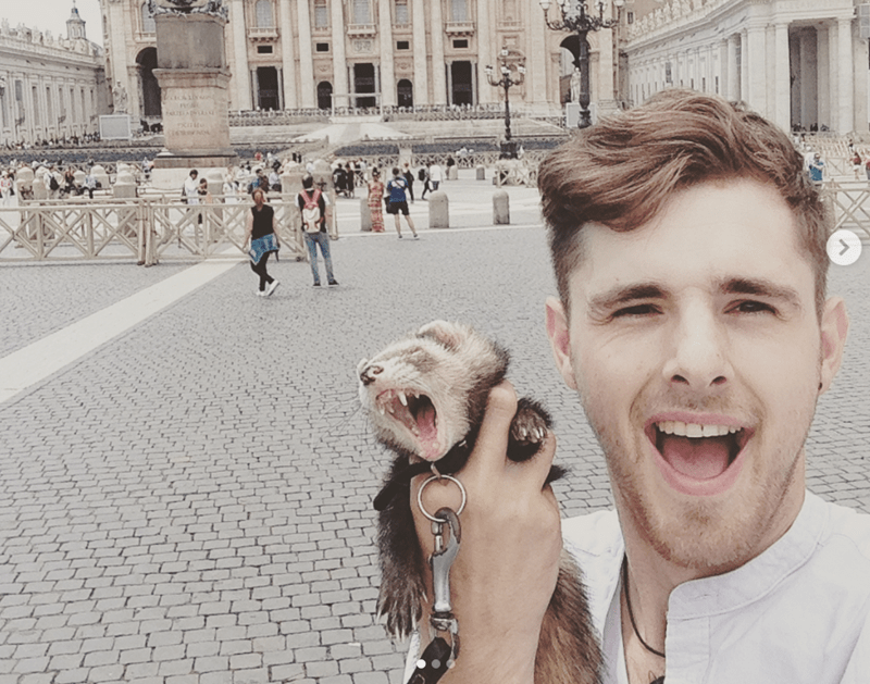 Guy Goes on a Journey of Self Discovery with his Pet Ferret | man taking a selfie while holding a ferret wearing a leash in a touristy area on a brick road