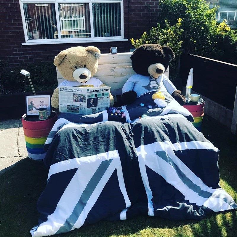 Teddy bears entertaining the neighbors | two large stuffed toys bear plushies arranged in a bed under the covers dressed in pajamas reading the newspaper and knitting