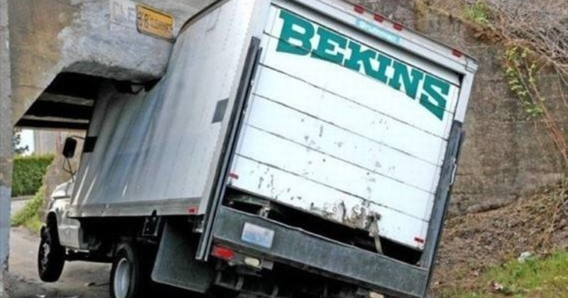 A collection of times that large trucks were absolute failures | BEKINS truck stuck under a concrete bridge after attempting to drive under it