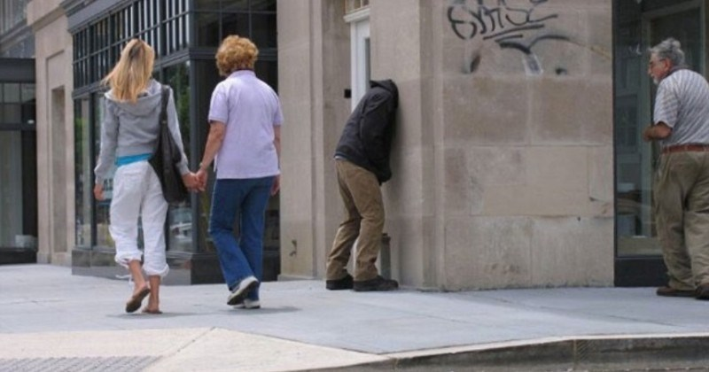 A collection of images showing times that mannequins were misplaced. | couple walking hand in hand in a street looking at a sculpture that looks like a person with their head stuck inside a wall