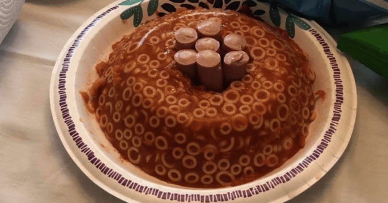 A collection of cursed food items that are just hard to look at | round cake made from jello spaghetti o's with sausages stuck in the middle