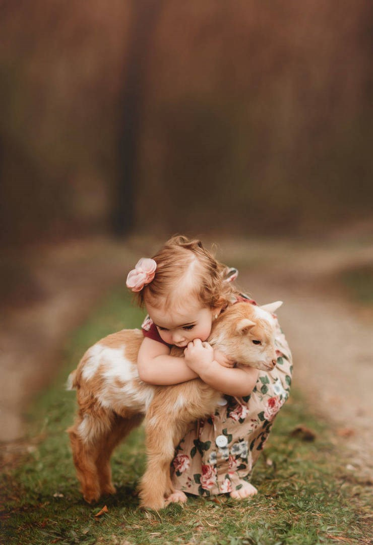 photography kids animals magic art photographer beautiful aww cute | adorable baby with red curls wearing a floral dress bending down to hug a tiny lamb with brown and white fur