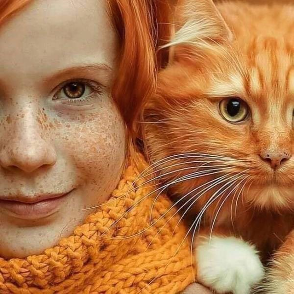 Amazing animal photos | cool photography pic of an orange cat with yellow eyes sitting on the shoulder of a freckled girl with red hair and an orange scarf both looking at the camera