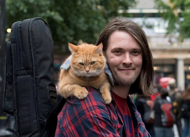 Tributes Are Poring Following The Death Of Street Cat Bob At The Age Of 14 | person with long hair smiling and looking at the camera with an orange cat sitting on their shoulder
