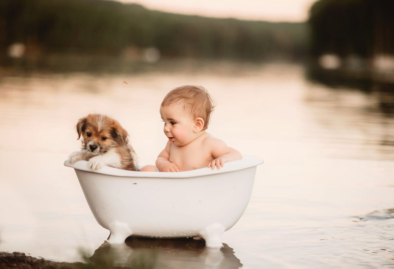 Photographer Celebrates The Joy Of Kids Cuddling With Similarly-Sized Pets | cute little baby and an adorable puppy dog sitting together in a tiny miniature bathtub