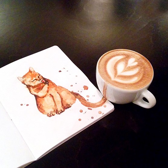 Cats as coffee types | cool creative art unusual illustration using coffee as paint to a cat in a notebook next to a cup of cappuccino