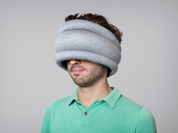 A picture of a man using the Ostrich Pillow. Cover image for things that will help you sleep while traveling