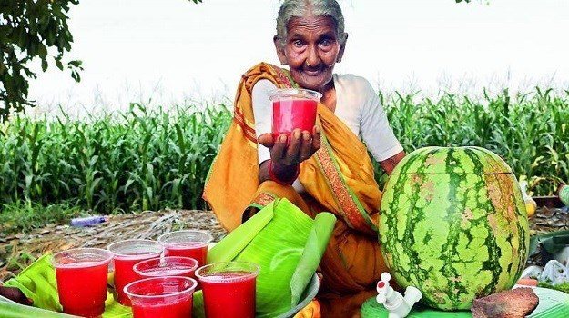 106 Year old Grandmother became Youtube sensation because of her recipes - cover photo of her offering fruit juices right out of a watermelon.