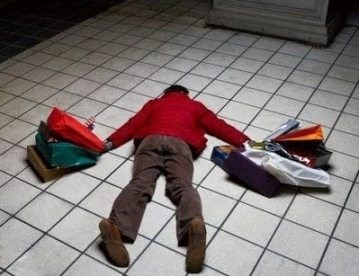 Photos of men suffering while shopping - Man passed out on the floor with shopping bags.