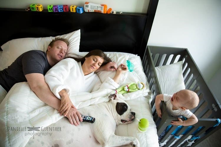 The real family life in photos - family passed out on the bed with dog as baby cries away.