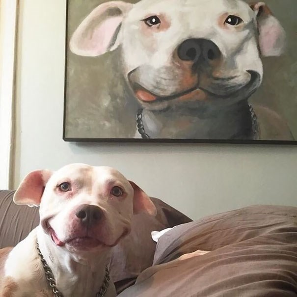 animals proving that life imitates art - Smiling dog with portrait behind him.