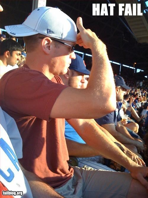 Funny picture in which a guy with a backwards baseball cap is using his hand to block the sun from his eyes so that he can see. Might be easier to just wear that hat correctly.