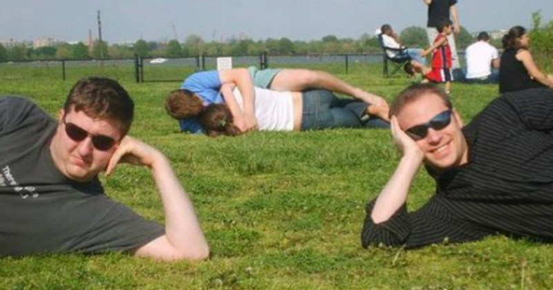 couple is making out on the grass while two guys pose in front of them -