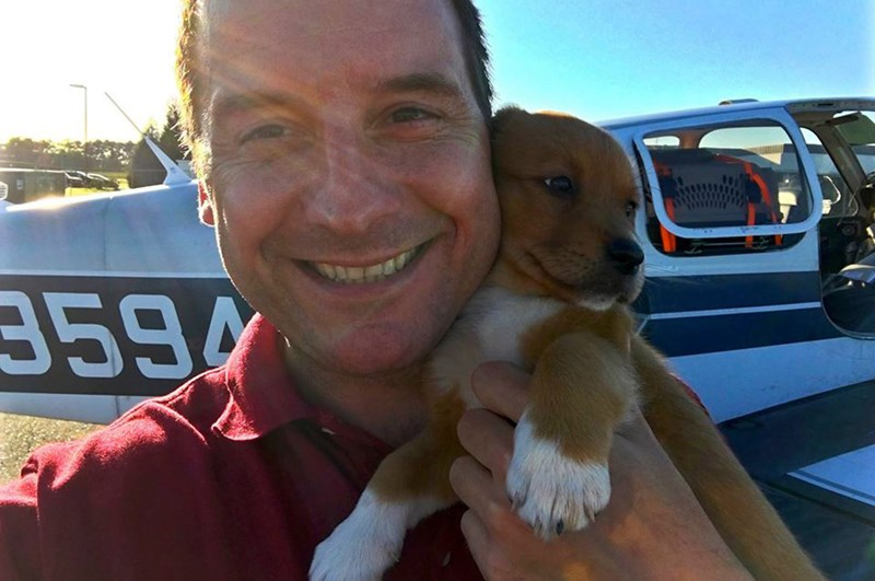a cute picture of paul holding a puppy he is rescuing - cover for a story about a man that has bought a plane to transfer animals from kill shelters to forever homes