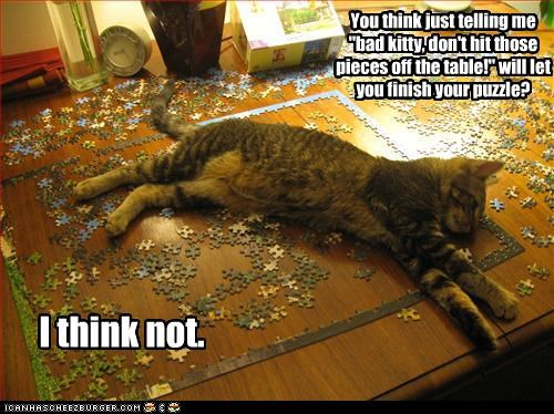 """You think just telling me """"bad kitty, don't hit those pieces off the table!"""" will let you finish your puzzle?"""