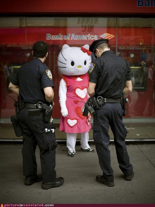 Funny picture of someone dressed as Hello Kitty getting a ticket or being questioned by the cops.