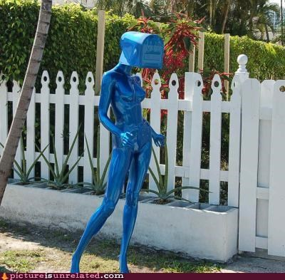 Mailbox on the head of a blue mannequin that is on someones lawn grass.