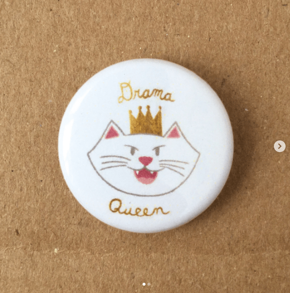 cute kitty pins | white pin with a drawing cartoon white cat wearing a golden crown and the writing drama queen