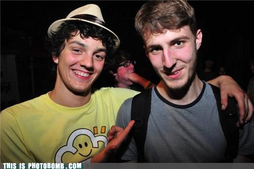 dumb hat,fist,glasses,mouthful,photobomb
