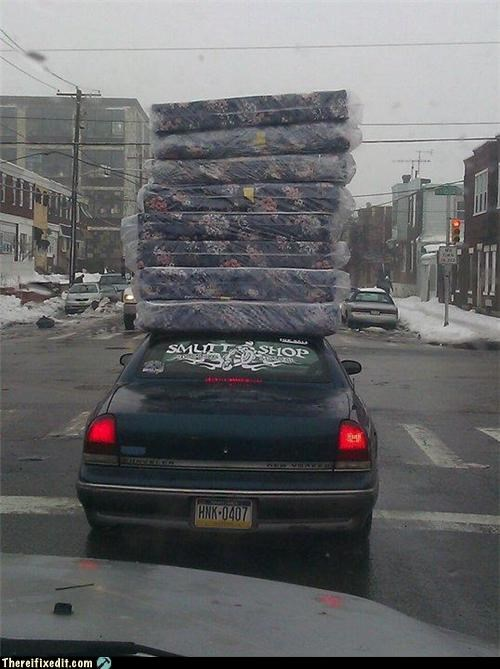 cars driving holding it up mattresses stacking