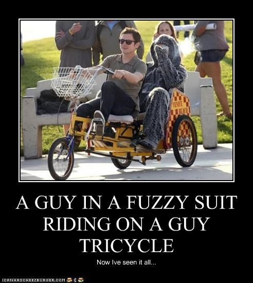 A GUY IN A FUZZY SUIT RIDING ON A GUY TRICYCLE Now Ive seen it all...