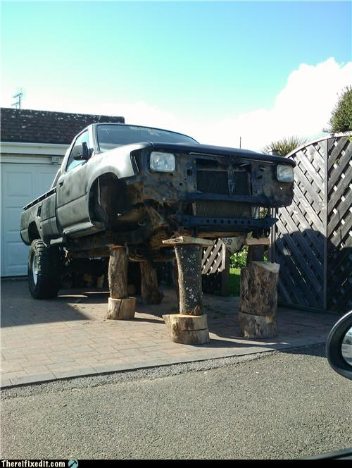 holding it up,jacked,stump,trees,trucks