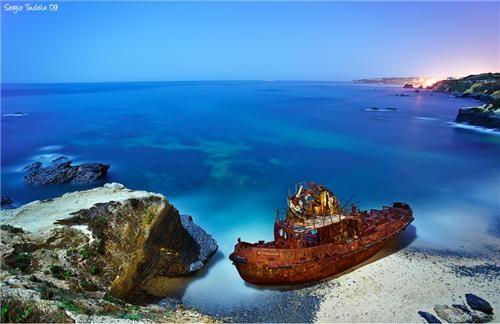beach side,blue water,boat,cliffs,europe,ocean,ocean side,portugal,rusted boat