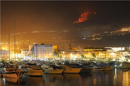black boats erupting eruption europe geographic formation getaways Hall of Fame harbor island Italy lava mediterranean night night photography orange sicily volcano white yellow - 5210130176
