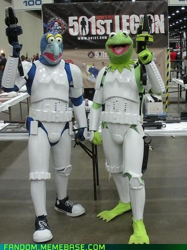 cosplayers at an event dressed like muppets kermit the frog and gonzo i star wars white stormtrooper armor and holding laser guns
