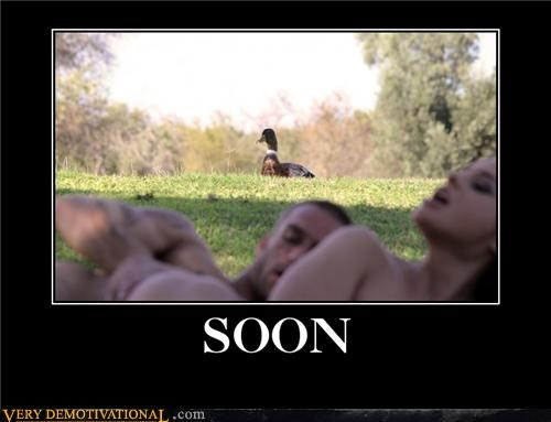 funny picture of people naked in the park and a duck in the background in focus with the caption, 'soon'.