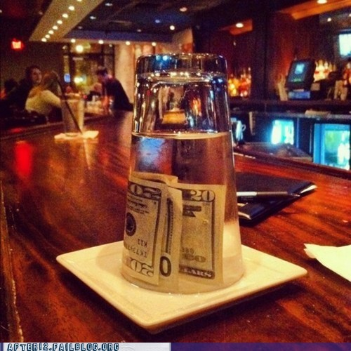 Fail tip giver of a tip inside a glass of water that is upside down and full of water with the money inside the the water. Hard to tell if good tipper or angry customer.