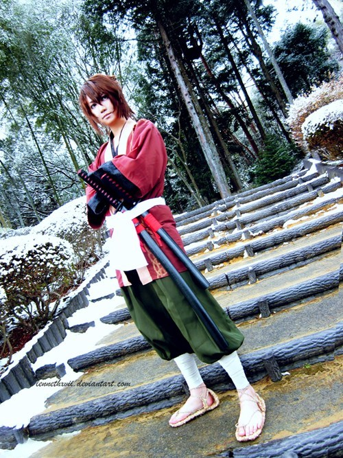 cosplay anime Fist Unit Captain-Souji Okita Hakuouki person in samurai like outfit red robe and green pants with bandaged legs carrying two swords in their belt