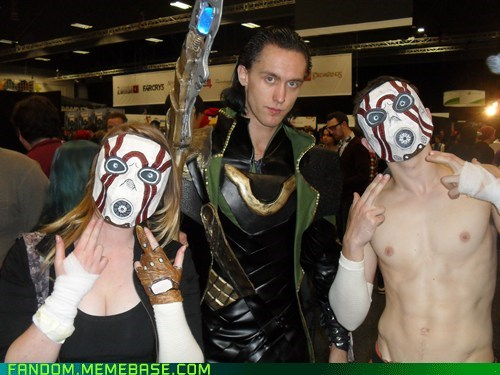 cosplayers loki from the avengers standing between two cosplayers characters from the game borderlands with face masks throwing hands signs