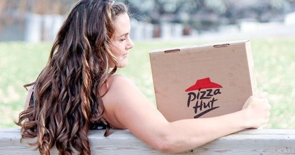 student take a photoshoot with a pizza hut box