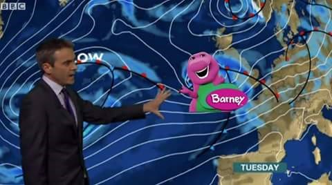 weatherman showing an approaching storm that looks like barney the dinosaur