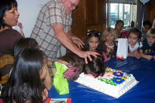 man shoving a child's face into a cake during a birthday party