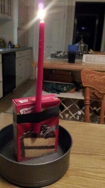 box of cake mix with a single burning candle taped to it