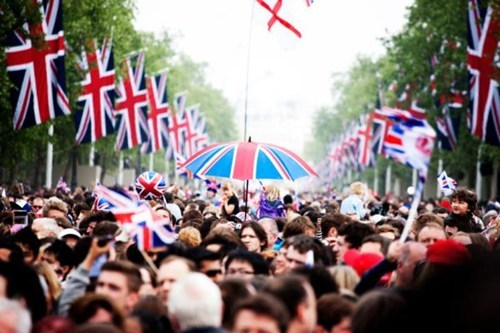 Many people walking in the street with the British flag waving.
