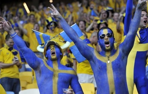 Shirtless dudes painted in yellow and blue in Sweden.