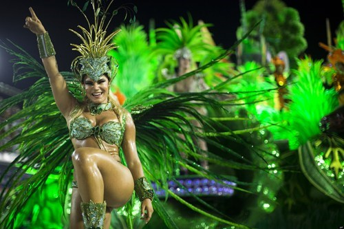 Lots of green in a picture of Brazil during Carnival, with dancer kicking her leg.