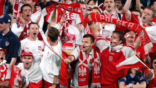 Poland sports fans shouting and waving their banners of red and white.