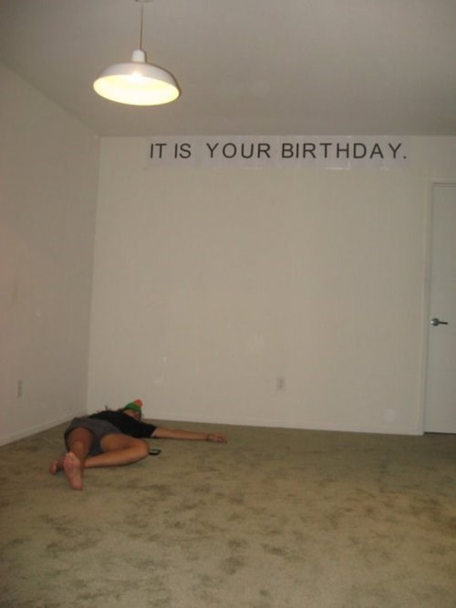 person wearing a party hat laying on the floor in a empty room under a sign that says it is your birthday