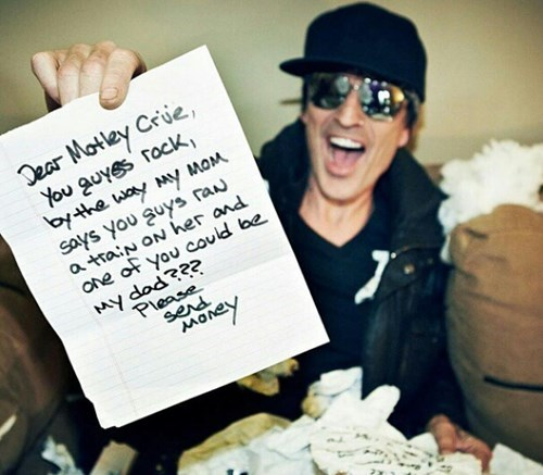 Picture of guy holding up a note to Motley Crue about how they ran a train on his mom a few years back and one of them might be his dad.