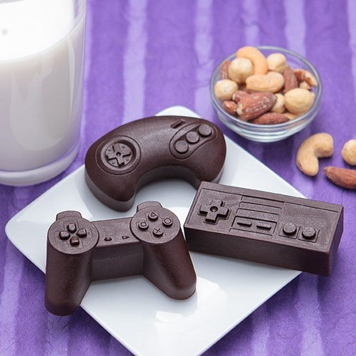 square white plate with three different shaped game controllers made of chocolate, a bowl of peanuts and cashews on the side
